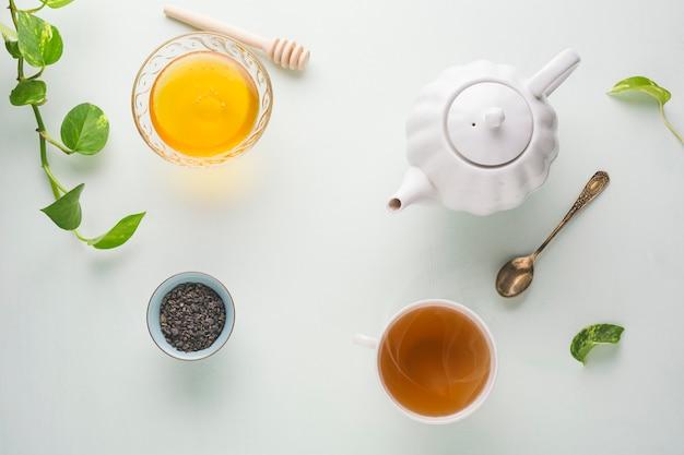 Свежесваренный чай, чайник и мед на светлом столе. белые блюда. светлый фон