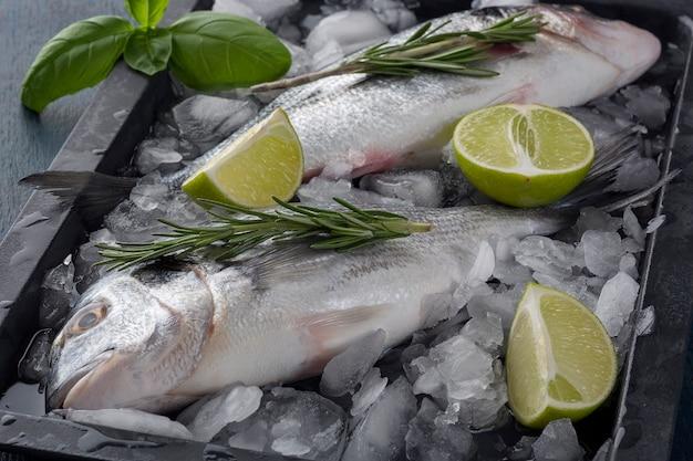 Свежая готовая к употреблению сырая рыба лещ дорадо с ингредиентами и приправами, такими как розмарин, соль, перец, лайм.