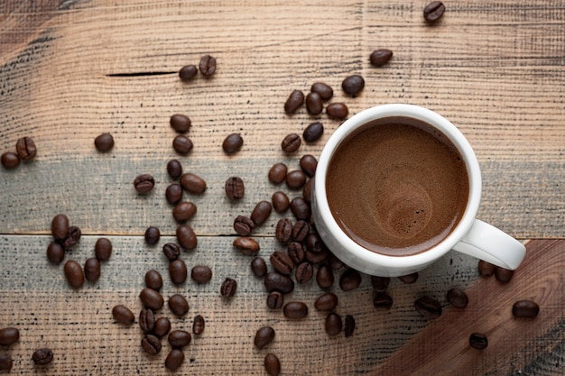 一杯のコーヒーとコーヒー豆をテーブルの上。木製の背景。上面図。