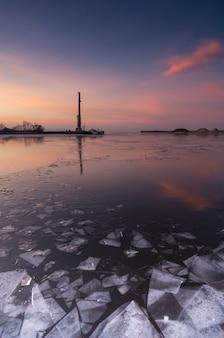 Лед на реке. зима. красивое закатное небо. отражения неба на льду.