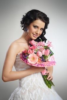 花の花束と白いウェディングドレスで美しい少女