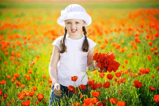 Счастливая маленькая девочка в маках солнечный день в парке