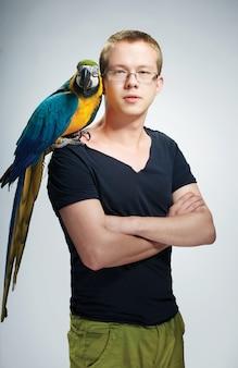 Парень с ярким попугаем на изразцовой печи