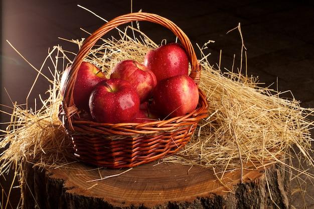 干し草で横になっているリンゴのバスケット