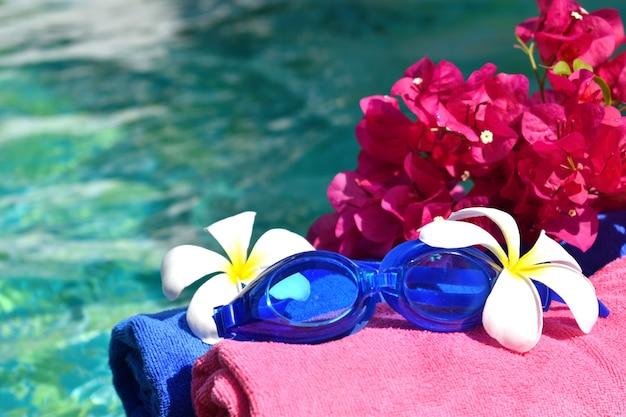 海でリラックスした休日。タオル、グラス、水の上の花。体の美容スパのコンセプト。