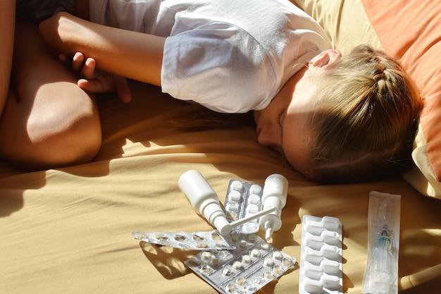 ベッドで悲しい病気の女児。子供のベッド近くの薬