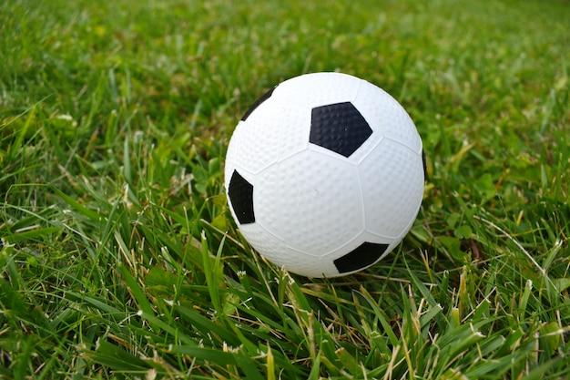 Ребенок играет в футбол. детский футбольный мяч на зеленой траве.