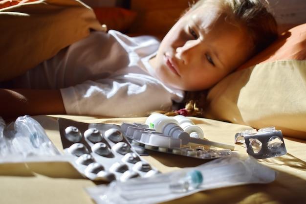 Больная девочка в постели с лекарствами. сезонные простуды у детей. детские болезни. домашнее лечение для ребенка. детские и таблетки.