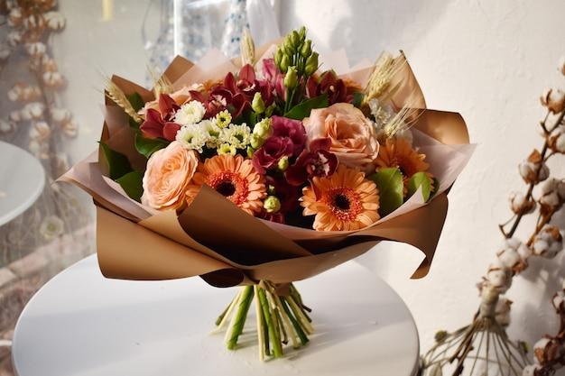 テーブルの上の花の花束。ウィンドウに色とりどりの花の美しい咲く花束。