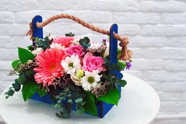 テーブルの上の美しいフラワーバスケット。色とりどりの花の美しい花束