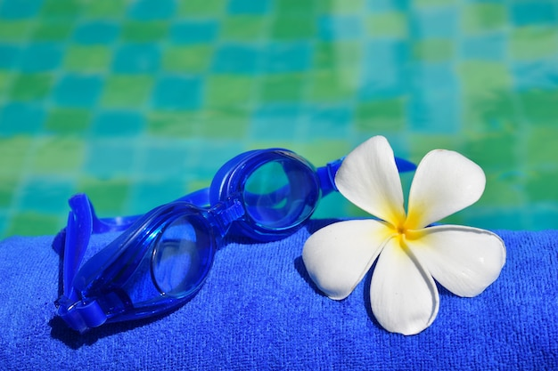 グラス、タオル、水の上の花。夏の時間とリラクゼーション。