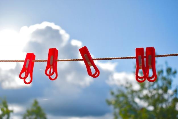 青い空にロープで赤い洗濯はさみ