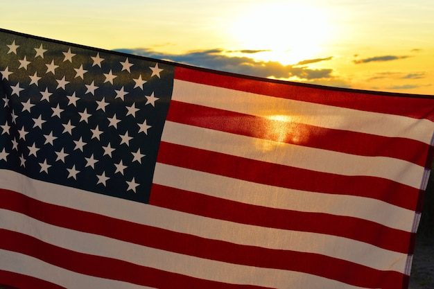 夕暮れ時の空にアメリカの国旗を振ってください。