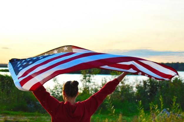 夕暮れ時の夕方にアメリカの国旗を持つ女性