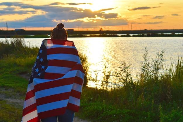 Женщина с американским флагом вечером на закате