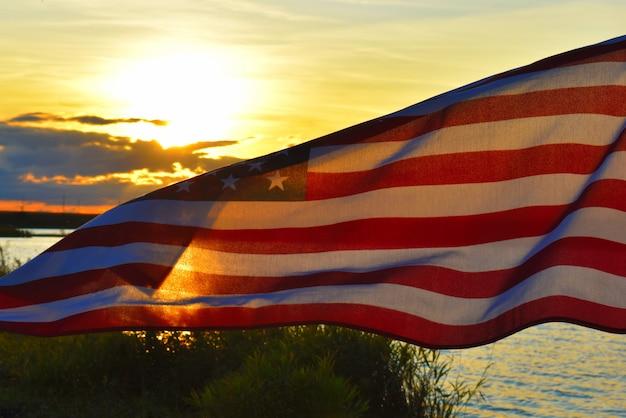 Размахивая американским флагом на небе на закате