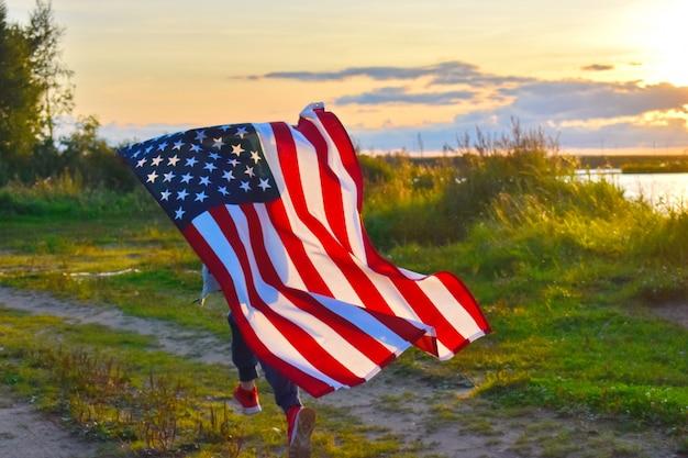 Ребенок бежит с американским флагом на закате