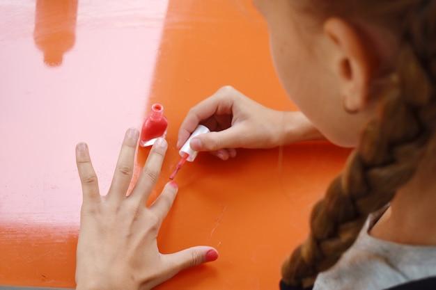 赤いマニキュアで彼女の爪を描く少女