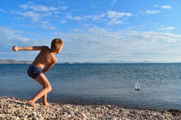 海に岩を投げる少年