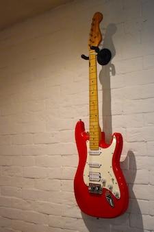 Красная электрогитара на кирпичной стене