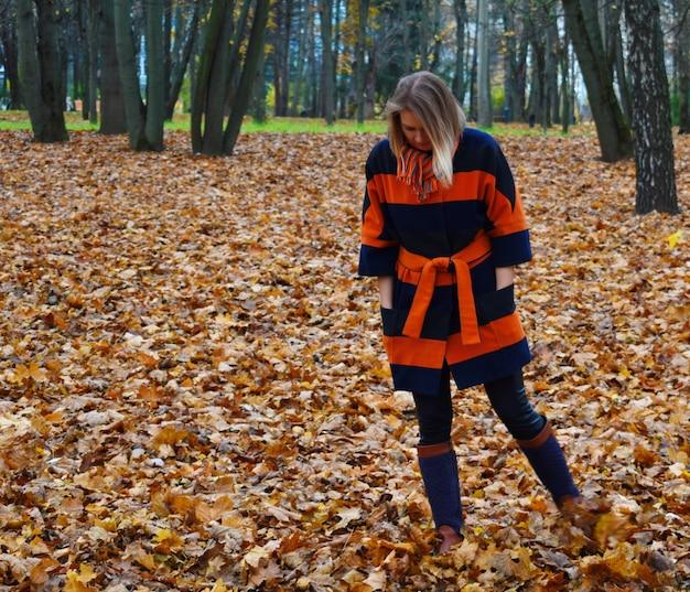 Женщина в пальто стоит в лесу