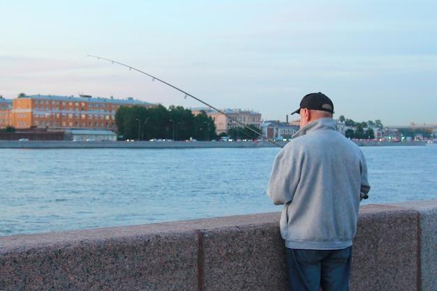 Человек, ловящий рыбу на городской набережной