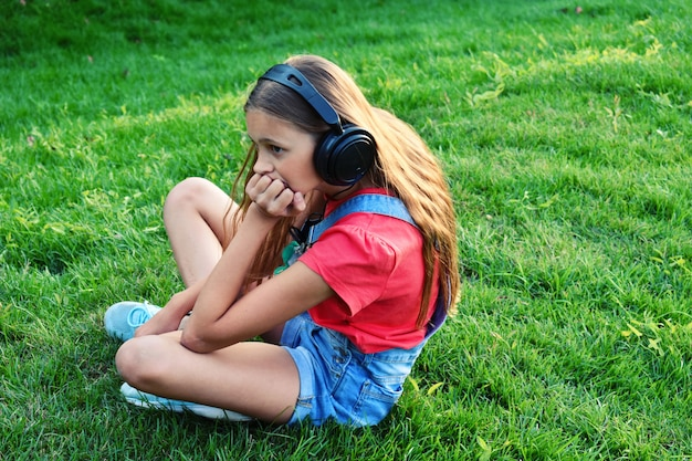 ヘッドフォン夏の屋外で悲しい少女