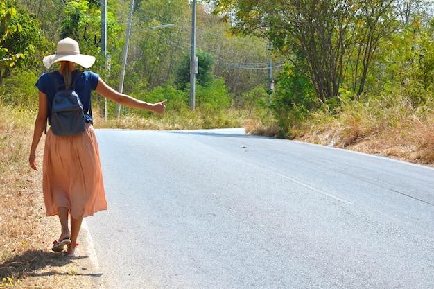 Красивая девушка ловит машину на дороге. женщина ждет машину. турист с рюкзаком стоял на дороге летом. путешествие автостопом в одиночку.