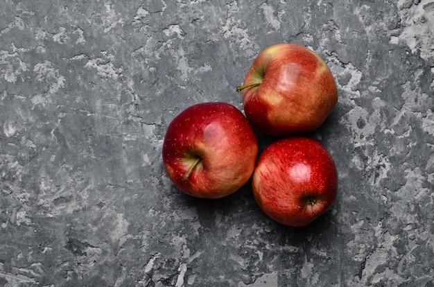 Красные спелые яблоки на бетонном столе. свежие фрукты. лофт и деревенский стиль. вид сверху
