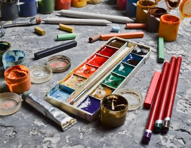 コンクリートのテーブルに描く製品。創造のためのインスピレーションの概念。色とりどりのガッシュ、オイル、水彩絵の具、クレヨン、鉛筆。