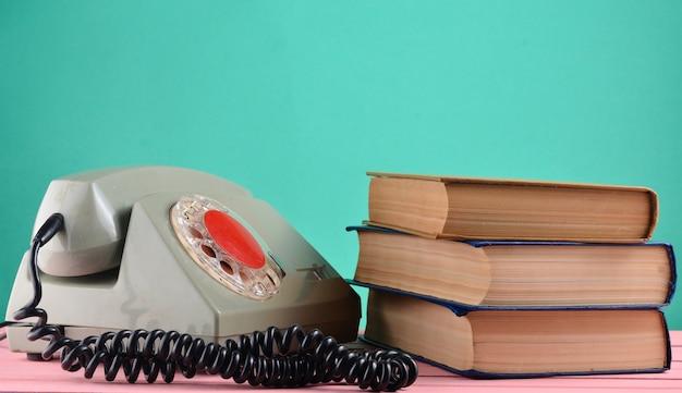 Ретро роторный телефон, стопка книг на столе, изолированных на фоне зеленой пастельной стены
