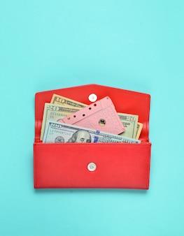 Купюры, аудиокассеты в красный кожаный кошелек на синем фоне пастельных. вид сверху