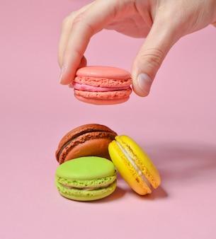 女性の手はピンクのマカロンクッキーを下げます。ピンクのパステル調の背景に多くのマカロン。ミニマリズム