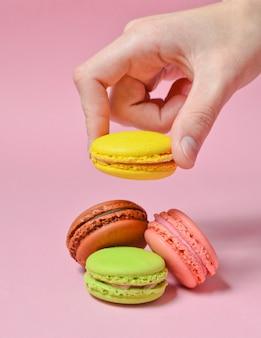 女性の手は黄色のマカロンクッキーを下げます。ピンクのパステル調の背景に多くのマカロン。ミニマリズム