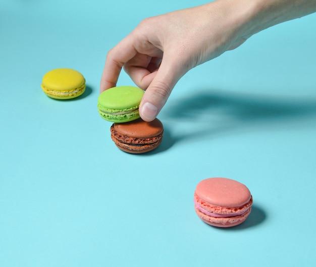 女性の手は緑のマカロンクッキーを下げます。青いパステル背景に色のマカロンのスタック。ミニマリズム