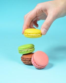 女性の手は黄色のマカロンクッキーを下げます。青いパステル背景に色のマカロンのスタック。ミニマリズム