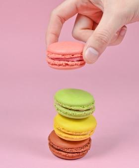 女性の手はピンクのマカロンクッキーを下げます。ピンクのパステル調の背景にマカロンのスタック。ミニマリズム
