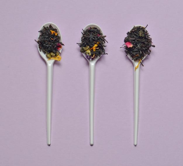 紫色の表面に乾燥茶葉のプラスチックスプーン