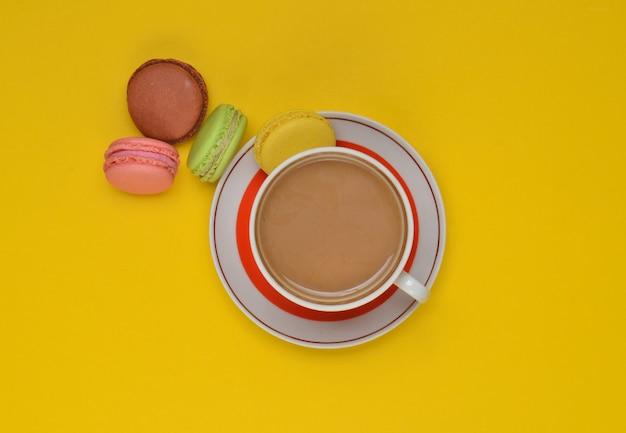 Чашка кофе, цветные миндальное печенье, на желтом фоне. вид сверху.