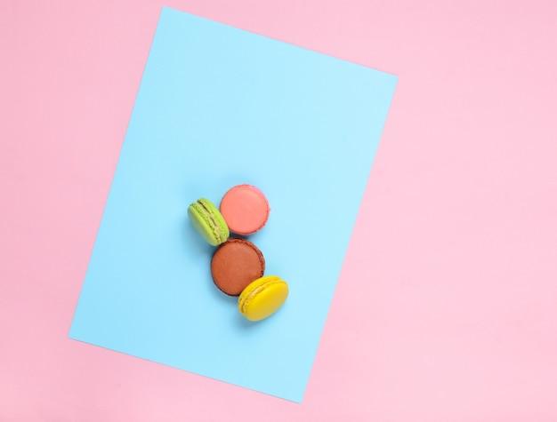 Цветные печенья миндальное печенье на розовом фоне пастельных синем. вид сверху. минимализм