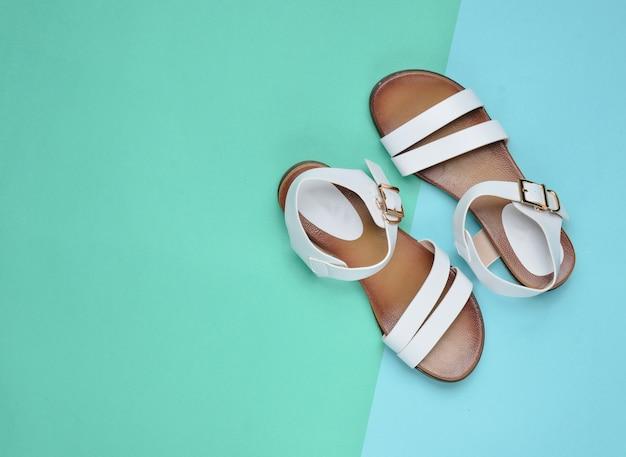 パステルカラーの表面、夏の靴、上面図、ミニマリズムのファッショナブルな革の女性のサンダル
