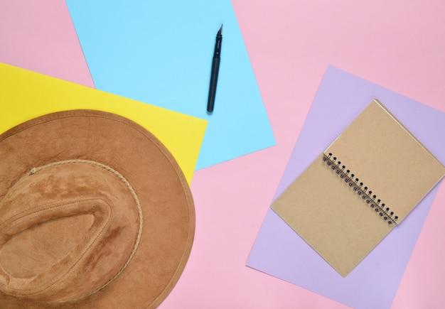 帽子、ノート、ペンを色紙の壁に感じた。旅行のコンセプトです。ミニマリズム、トップビュー