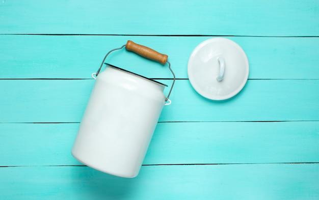 エナメルを塗った牛乳は青い木製の背景にすることができます。上面図