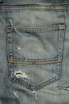 Задний карман потертых джинсов