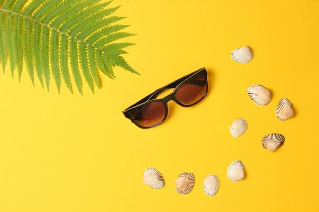 Лист папоротника, солнцезащитные очки, раковины на желтом фоне пастельных. концепция путешествия, туризм, пляжный курорт. лето. вид сверху, копия пространства