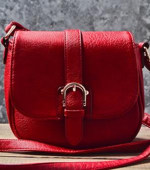 Красная кожаная сумка на деревянной полке против серой бетонной стены.