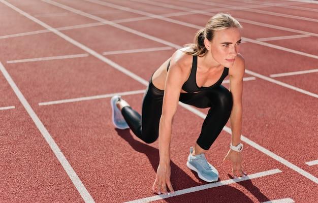 若いやる気のある女性ランナーがロースタート屋外でスプリントを実行する準備