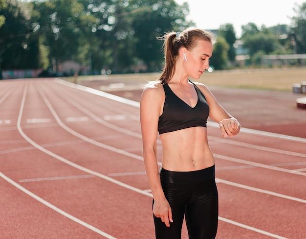 スポーツウェアの若い陽気な女性ランナーは赤コーティングされたスタジアムの屋外でスマートな時計を見てください。