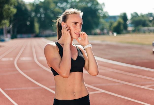 Молодая жизнерадостная бегунья в спортивной одежде слушает музыку в наушниках на стадионе с красной обивкой на открытом воздухе
