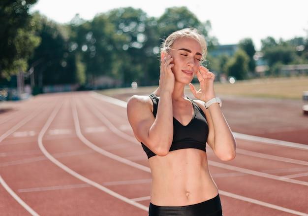 Молодая жизнерадостная бегунья в спортивной одежде слушает музыку в наушниках на красной дорожке стадиона на улице